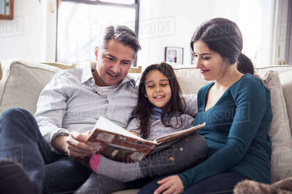 Girl with father and mother reading book while sitting on sofa at home Royalty-free stock photo