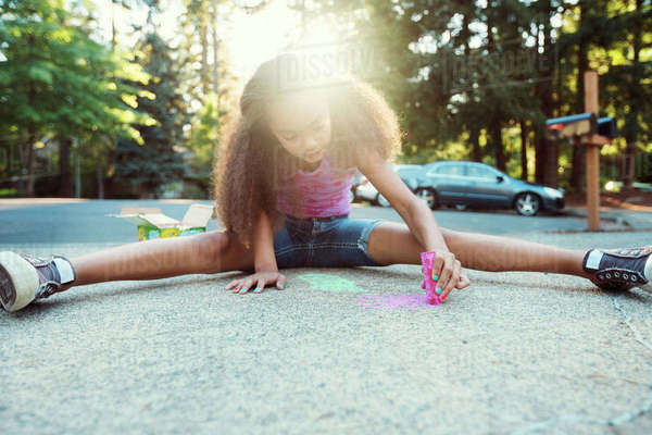 Full length of girl drawing with chalk on road Royalty-free stock photo