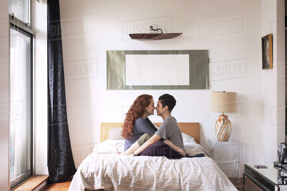 bedroom side view. Side View Of Romantic Lesbians Rubbing Noses While Sitting On Bed Bedroom O