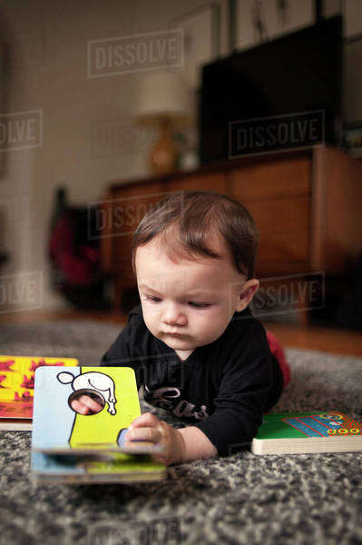 Small boy (6-11 months) with book on carpet Royalty-free stock photo