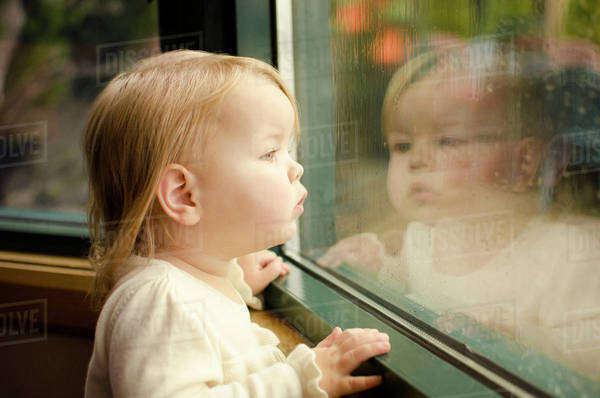 Baby girl (18-23 months) looking through window Royalty-free stock photo