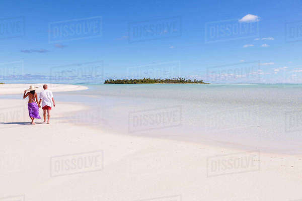 Rear view of couple walking at beach against blue sky during sunny day Royalty-free stock photo