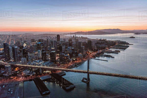 Aerial view of Oakland Bay Bridge over sea by city during sunset Royalty-free stock photo