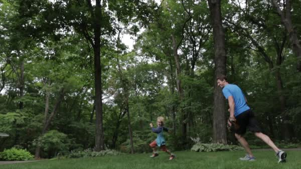 Cheerful father chasing son while playing baseball at yard Royalty-free stock video