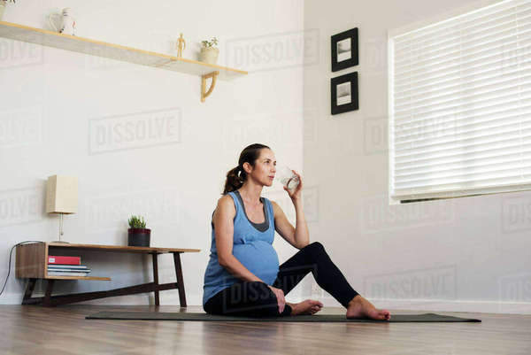 Pregnant woman drinking water while sitting on exercise mat at home Royalty-free stock photo