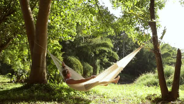 Lockdown shot of man with arms raised swinging in hammock at forest Royalty-free stock video