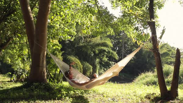 Lockdown shot of man swinging while relaxing in hammock at forest Royalty-free stock video