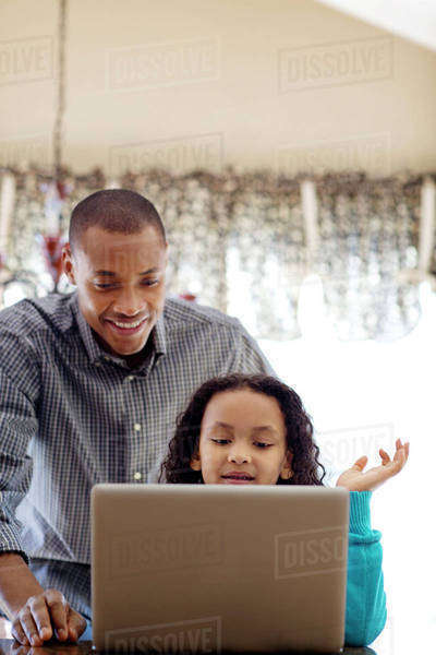 Father and daughter (6-7) using laptop at home Royalty-free stock photo