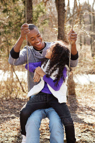 Father and daughter (6-7) laughing on swing Royalty-free stock photo