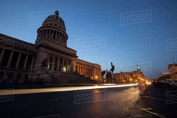 Light trails on city street by Capitolo building against clear blue sky at dusk Royalty-free stock photo