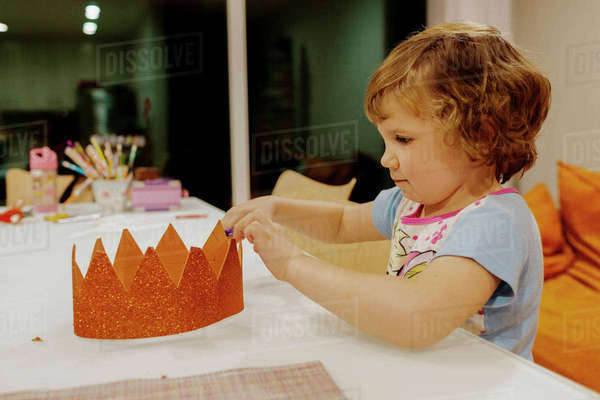 Girl making crown at dining table Royalty-free stock photo
