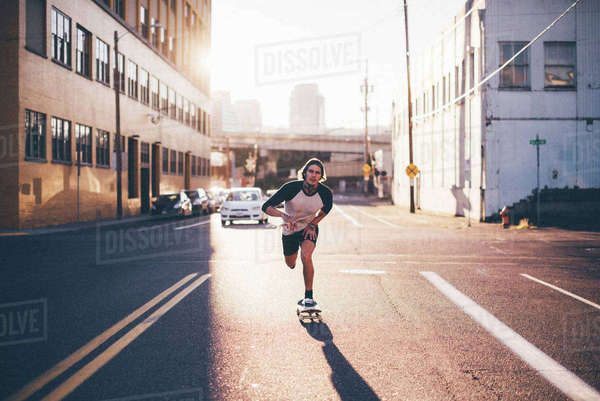 Portrait of man skateboarding on city street against sky during sunny day Royalty-free stock photo