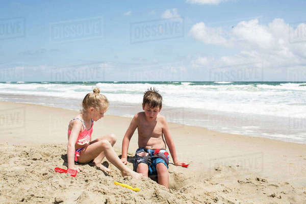 Siblings playing with sand at beach against sky during sunny day Royalty-free stock photo