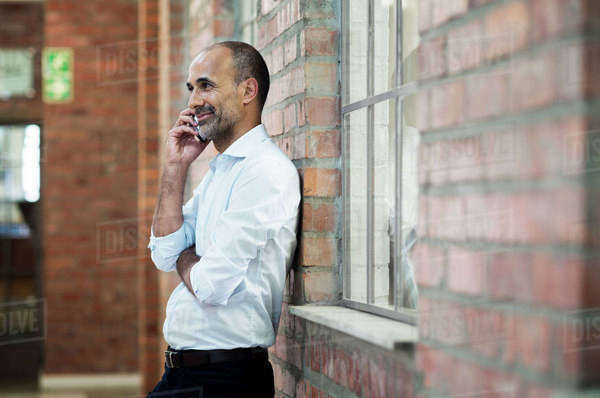 Side view of businessman talking on smart phone while standing against brick wall Royalty-free stock photo