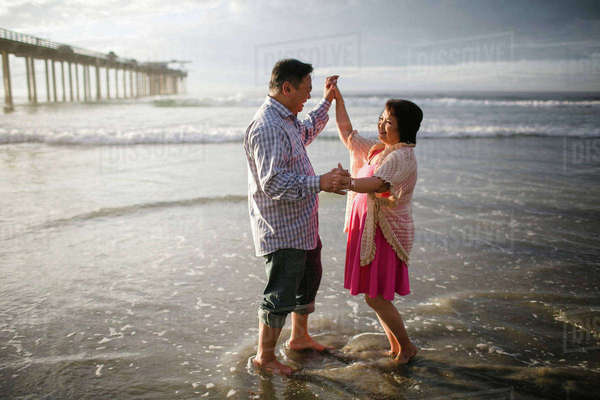 Side view of couple dancing on shore at beach Royalty-free stock photo