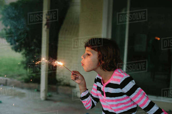Girl blowing burning sparkler while playing in backyard Royalty-free stock photo