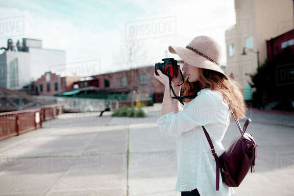 Side view of woman photographing while standing on footpath in city Royalty-free stock photo