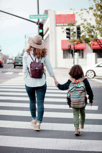 Rear view of woman holding boy's hand while crossing road in city Royalty-free stock photo