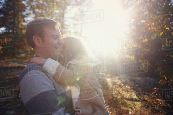 Happy father carrying daughter while standing at park during sunny day Royalty-free stock photo