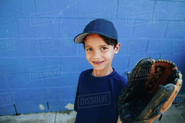 Portrait of happy boy wearing baseball glove standing against wall Royalty-free stock photo