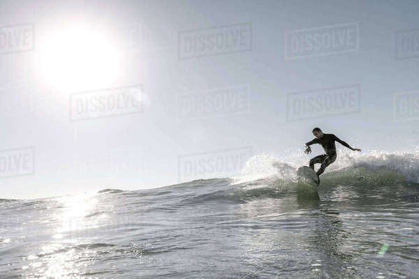 Mid adult man surfing on huge wave in sea against clear sky during sunny day Royalty-free stock photo