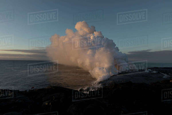 Smoke emitting from volcano at beach against sky during sunset Royalty-free stock photo