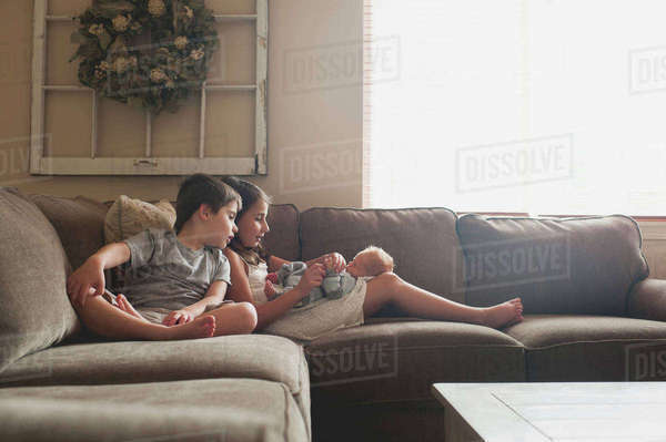 Siblings playing on baby boy while sitting on sofa at home Royalty-free stock photo