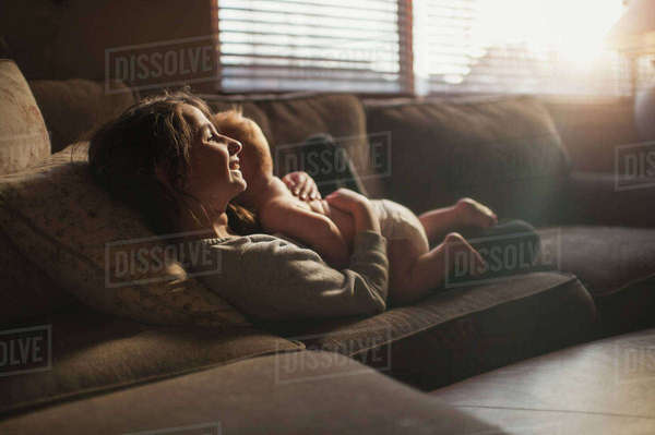 Smiling girl embracing brother while reclining on sofa at home Royalty-free stock photo