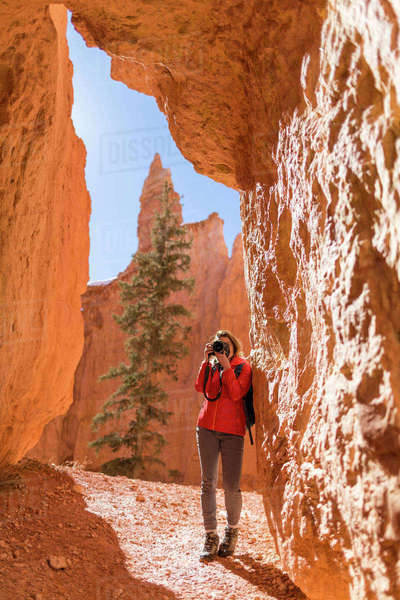 Hiker photographing while standing by rock formations at Bryce Canyon National Park Royalty-free stock photo