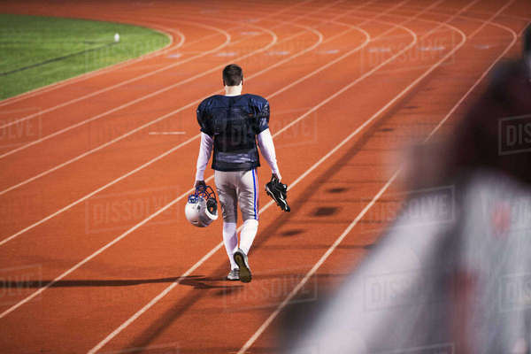 Rear view of American football player walking on sports track in stadium Royalty-free stock photo