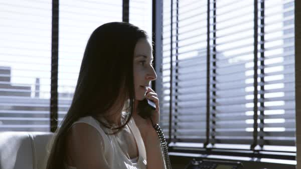 Dolly shot of businesswoman talking on landline phone while working in office Royalty-free stock video