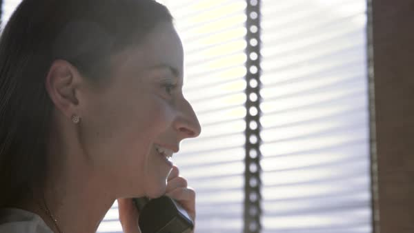 Dolly shot of businesswoman using landline phone in office Royalty-free stock video