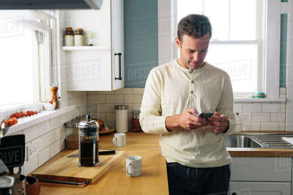 Man using smart phone while leaning by kitchen counter at home Royalty-free stock photo