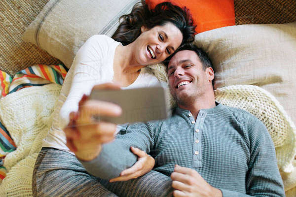 Overhead view of couple taking selfie while lying on carpet at home Royalty-free stock photo