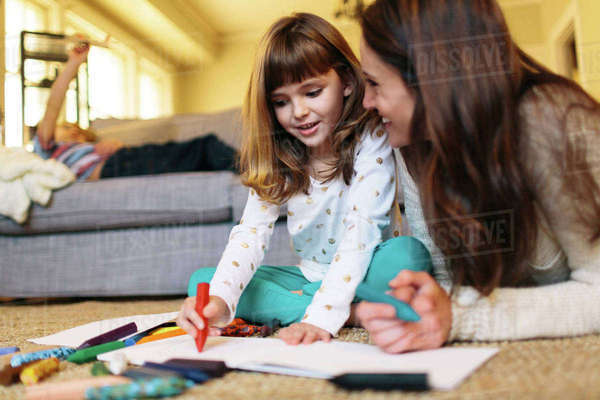 Mother looking at girl drawing on paper Royalty-free stock photo
