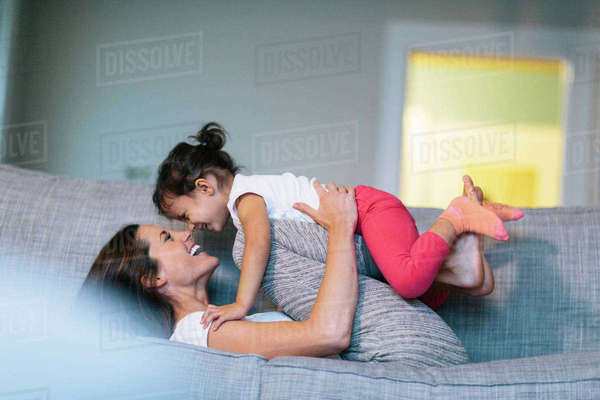 Side view of woman playing with girl on sofa at home Royalty-free stock photo