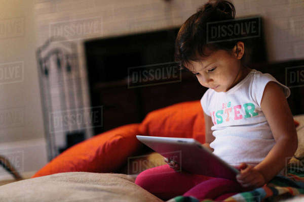 Girl using tablet computer while kneeling at home Royalty-free stock photo
