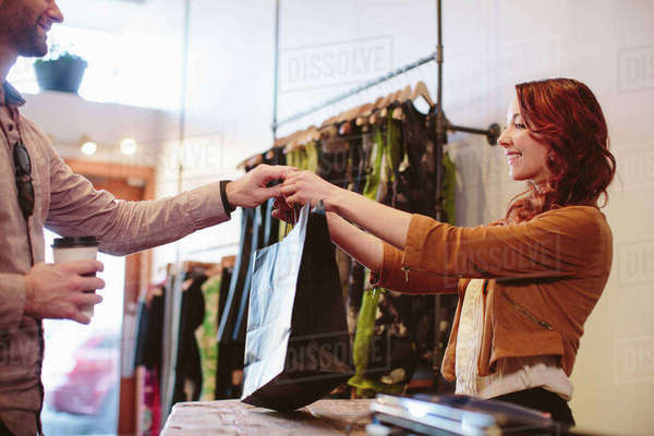 Smiling owner giving shopping bag to customer in store Royalty-free stock photo