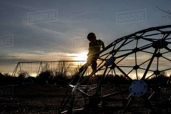 Silhouette boy playing on jungle gym in playground against cloudy sky during sunset Royalty-free stock photo