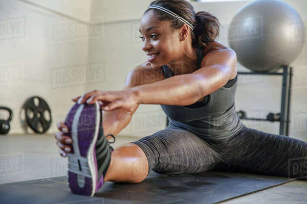 Smiling athlete stretching legs on exercise mat in health club Royalty-free stock photo