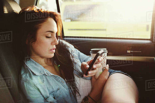 Woman with disposable cup using mobile phone while traveling in car Royalty-free stock photo
