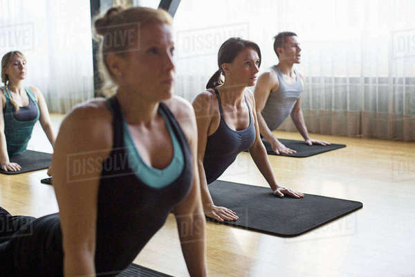 Women with male instructor practicing upward facing dog position in gym Royalty-free stock photo