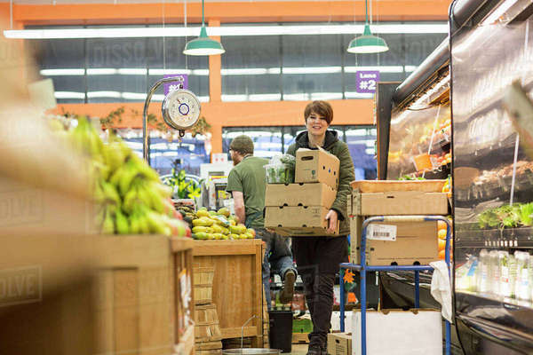 Female worker carrying boxes while working at supermarket Royalty-free stock photo