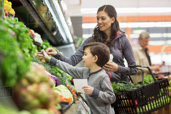 Mother and son shopping for vegetables at supermarket Royalty-free stock photo