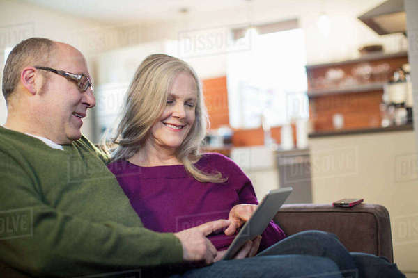 Smiling couple using tablet computer while sitting on sofa at home Royalty-free stock photo