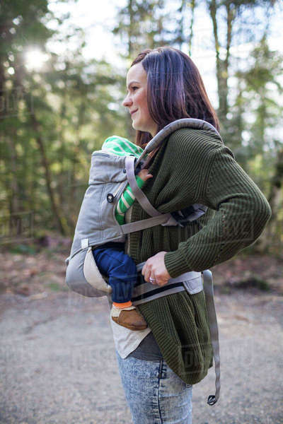 Side view of mother with son in baby carrier standing on footpath Royalty-free stock photo