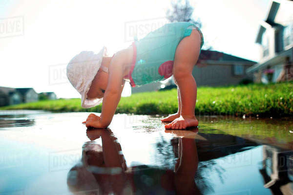 Side view of playful baby girl bending on puddle in backyard Royalty-free stock photo