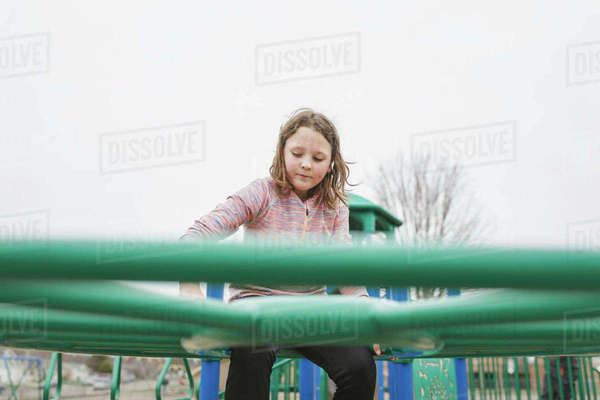 Low angle view of girl climbing on jungle gym against clear sky at playground Royalty-free stock photo