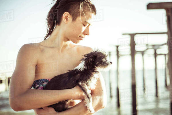 Woman in bikini carrying puppy at beach against sky Royalty-free stock photo