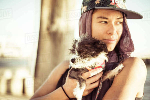 Woman wearing cap carrying puppy at beach Royalty-free stock photo